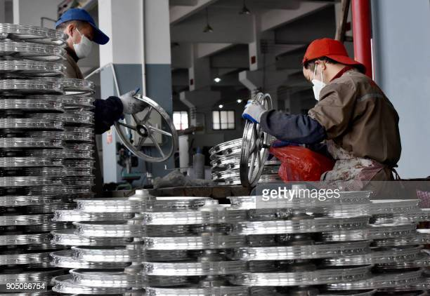 This photo taken on January 14 2018 shows Chinese employees working on bicycle parts made for sharing bicycles at a factory in Jinhua in China's...