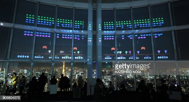 This photo taken on January 15 2018 shows Space Invaders GigaMax video game being displayed on the windows of the Roppongi Hills observatory Tokyo...