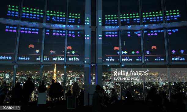 TOPSHOT This photo taken on January 15 2018 shows Space Invaders GigaMax video game being displayed on the windows of the Roppongi Hills observatory...