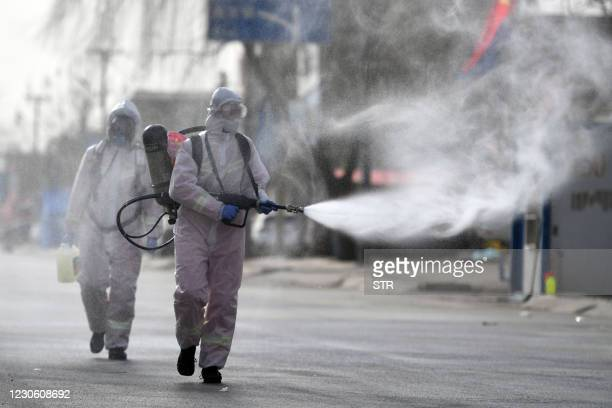 This photo taken on January 15, 2021 shows people in protective suits spraying disinfectant on a street at Gaocheng district, which was declared a...
