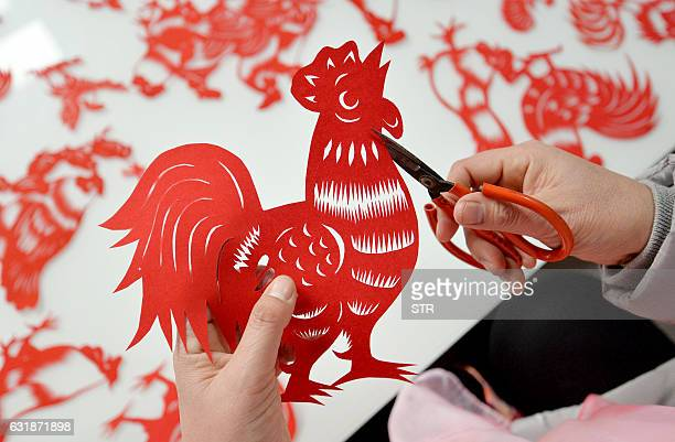 This photo taken on January 16 2017 shows folk craftsman Feng Shiping making a paper cutting of a rooster for the upcoming Chinese New Year in Handan...