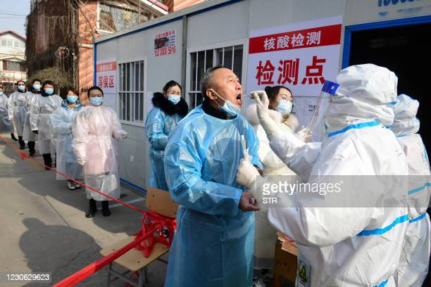 This photo taken on January 16, 2021 shows residents undergoing Covid-19 coronavirus tests at a makeshift testing centre inside a residential...