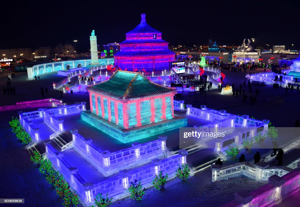 This photo taken on January 2, 2018 shows people visiting the Harbin Ice-Snow World in Harbin in China's northeastern Heilongjiang province. The city will host on January 5 the Harbin Ice and Snow Sculpture Festival, which attracts hundreds of thousands of visitors annually. / AFP PHOTO / - / China OUT