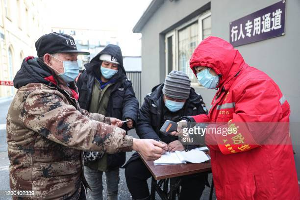This photo taken on January 2, 2021 shows a man having his temperature taken before being tested for the Covid-19 coronavirus at a temporary testing...