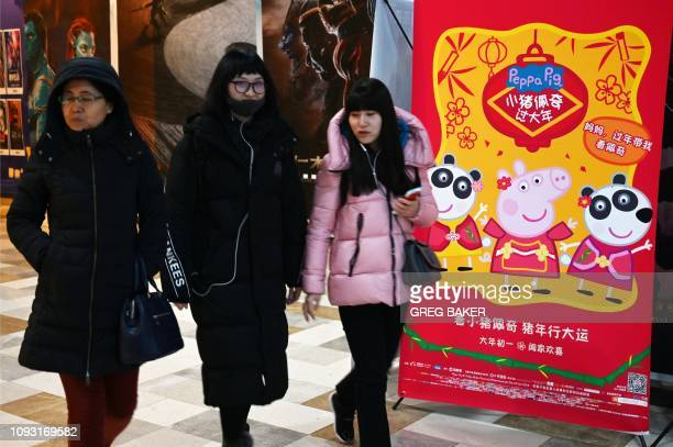This photo taken on January 21 2019 shows women walking past a poster for the Peppa Pig movie at a theatre in Beijing Roasted as a subversive symbol...