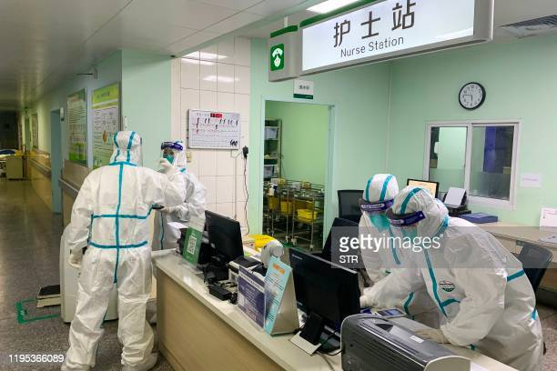 This photo taken on January 22, 2020 shows medical staff members wearing protective suits at the Zhongnan hospital in Wuhan in China's central Hubei...