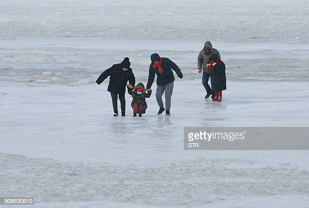 This photo taken on January 23 2016 shows people playing on the frozen waters of an offshore beach in Dalian in northeast China's Liaoning province...