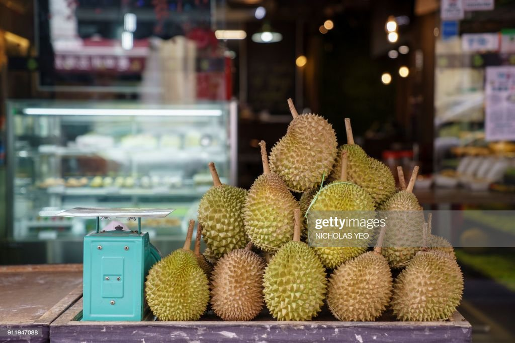 This photo taken on January 23, 2018 shows durian fruit outside Mao Shan Wang cafe in the Chinatown district of Singapore. The Singapore eatery centred around the pungent tropical fruit durian has caught a whiff of success as patrons flock to the cafe in droves for a bite of its exotic offerings. / AFP PHOTO / Nicholas YEO