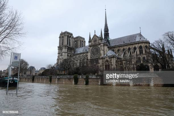 This photo taken on January 23 2018 shows the flooded banks of the Seine river next to Notre Dame cathedral in Paris The Seine river burst its banks...