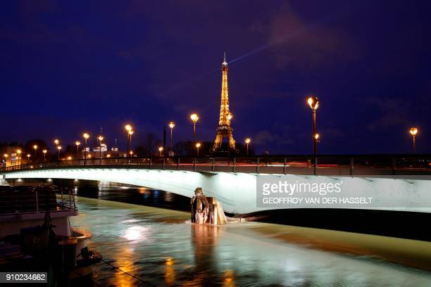TOPSHOT This photo taken on January 25 2018 in Paris shows an illuminated Eiffel Tower next to the Seine River with water levels raised to the height...