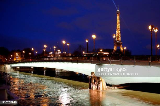 This photo taken on January 25 2018 in Paris shows an illuminated Eiffel Tower next to the Seine River with water levels raised to the height of the...