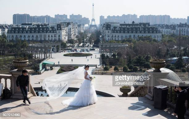 This photo taken on January 26 2016 shows a young Chinese couple posing for wedding photos in front of Parisianstyle architecture at Tianducheng a...