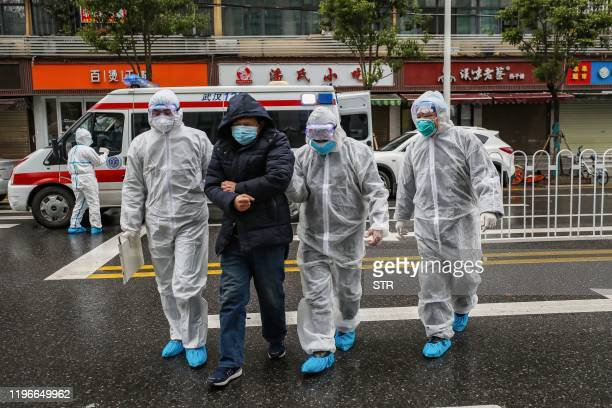 TOPSHOT This photo taken on January 26 2020 shows medical staff members wearing protective clothing to help stop the spread of a deadly virus which...