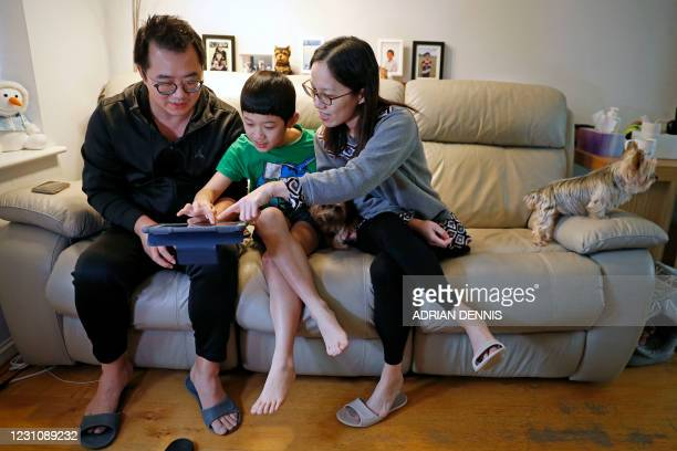 This photo taken on January 26, 2021 shows Winston Wong , who arrived in Britain last year from Hong Kong, and his wife Connie Chan with their son...