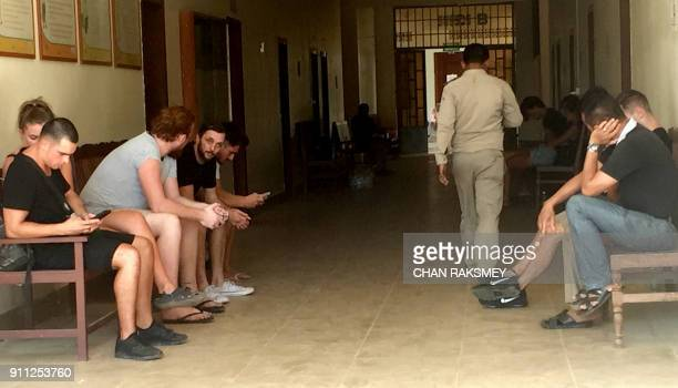 This photo taken on January 27 2018 shows a group of foreigners outside a courtroom in Siem Reap province some who were reportedly arrested on...