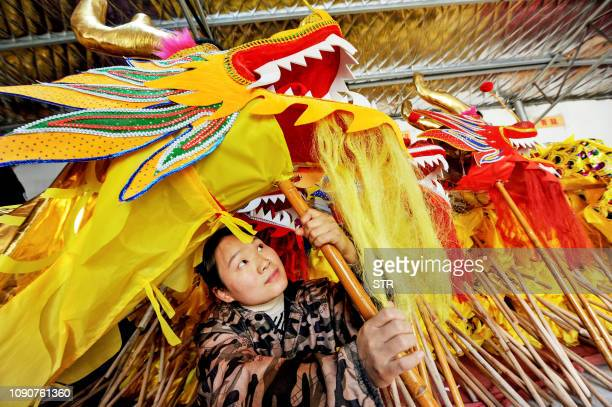 This photo taken on January 27 2019 shows a woman checking a dragon costume made for dragon dance ahead of the Lunar New year in Boyang in China's...