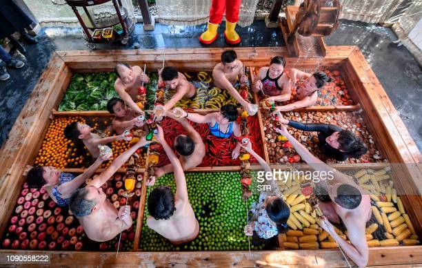 This photo taken on January 27 2019 shows people enjoying a dip in a hotpotshaped hot spring pool at a hotel in Hangzhou in China's Zhejiang province...