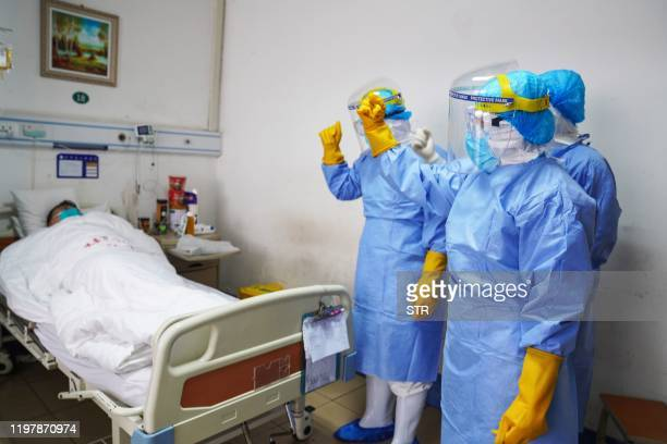 This photo taken on January 28 2020 shows medical staff members cheering up a patient infected by the novel coronavirus in an isolation ward at a...