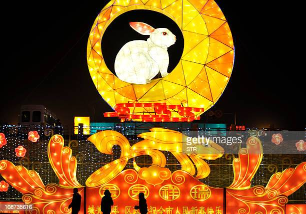 This photo taken on January 29 2011 shows pedestrians walking past a decoration for the upcoming Lunar New Year or the 'Year of the Rabbit'...