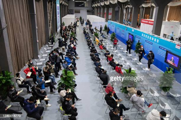 This photo taken on January 3, 2021 shows people waiting to receive COVID-19 coronavirus vaccines at a temporary vaccination centre in Beijing, as...