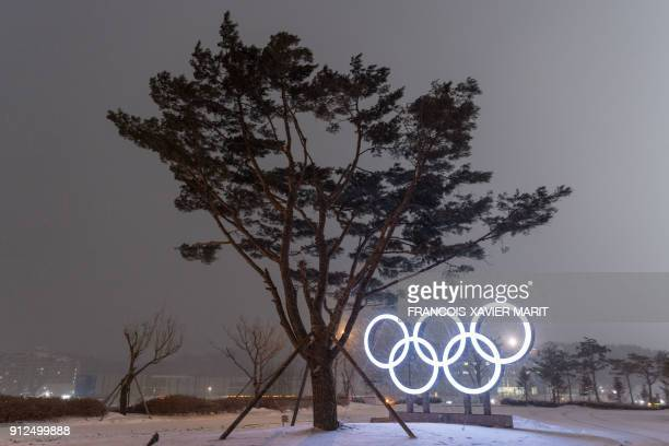 TOPSHOT This photo taken on January 30 2018 shows snow falling as the Olympic Rings are illuminated at night in PyeongChang ahead of the Winter...