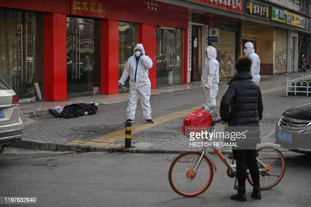This photo taken on January 30 2020 shows officials in protective suits checking on an elderly man wearing a facemask who collapsed and died on a...