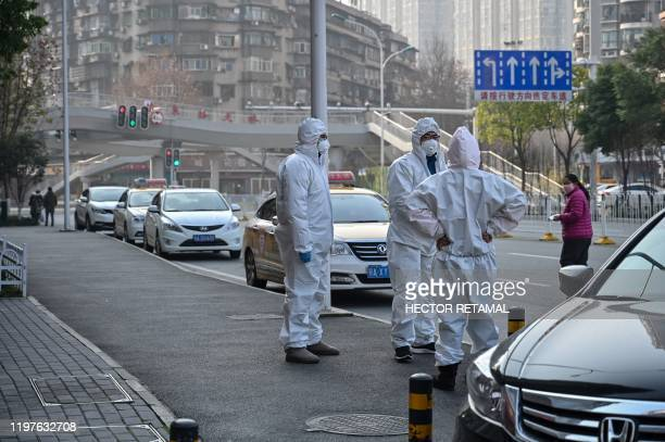 This photo taken on January 30, 2020 shows officials in protective suits gathered on a street after an elderly man wearing a facemask collapsed and...