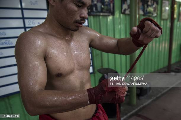 This photo taken on January 31 2018 shows the current World Boxing Council miniflyweight champion Wanheng Menayothin adjusting his handwraps during a...
