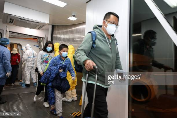 This photo taken on January 31 2020 shows people disembarking from a Xiamen Airlines plane after arriving from the Thai capital Bangkok at Tianhe...