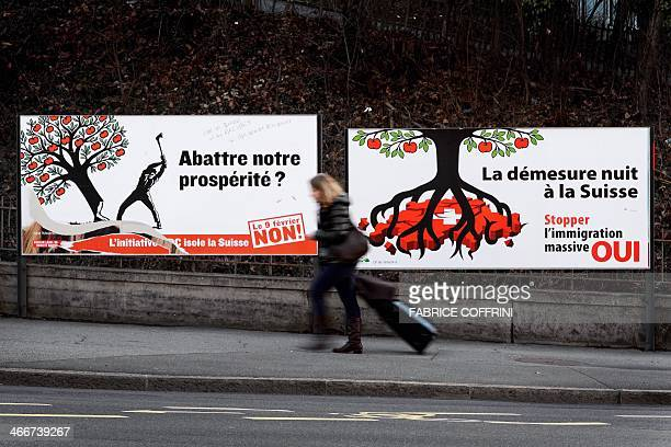 This photo taken on January 31 shows a woman pulling her luggage as she walks past two electoral posters against and in favor of a Stop Mass...