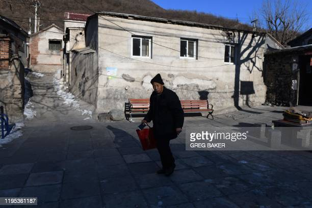 This photo taken on January 8 2020 shows shows a man walking in a village outside the Datai coal mine in Mentougou west of Beijing