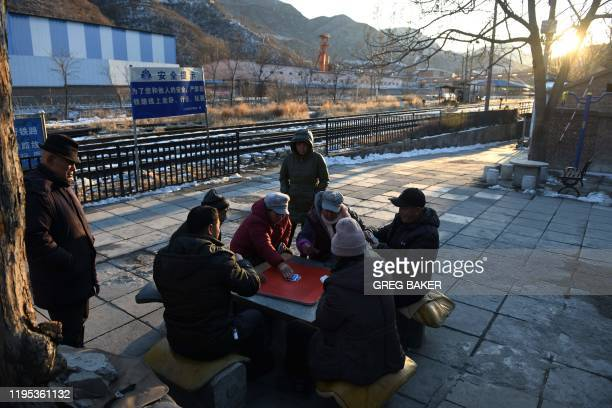 This photo taken on January 8 2020 shows shows residents playing cards in their village outside the Datai coal mine in Mentougou west of Beijing