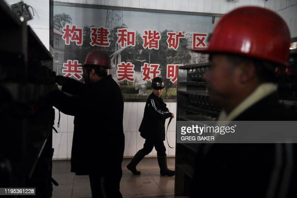 This photo taken on January 8 2020 shows workers putting away equipment after coming out of the Datai coal mine in Mentougou west of Beijing