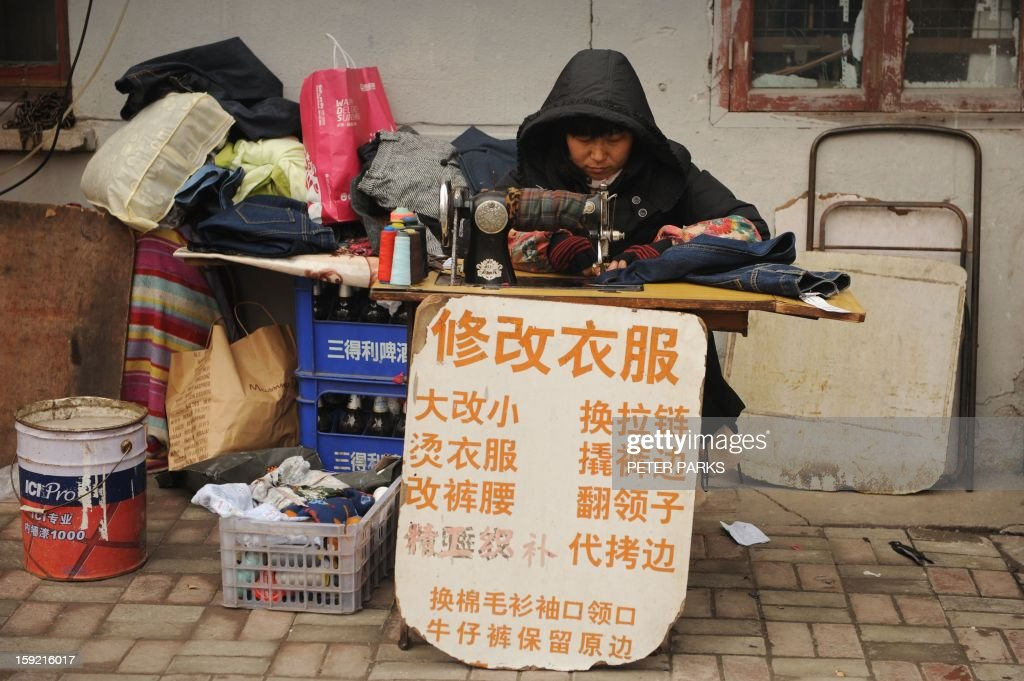 This photo taken on January 9, 2013 shows a woman sewing clothes on a street in Shanghai. China's trade surplus surged 48.1 percent to 231.1 billion USD in 2012 from the previous year, though total trade volume grew at a much slower pace, official data showed. AFP PHOTO/Peter PARKS