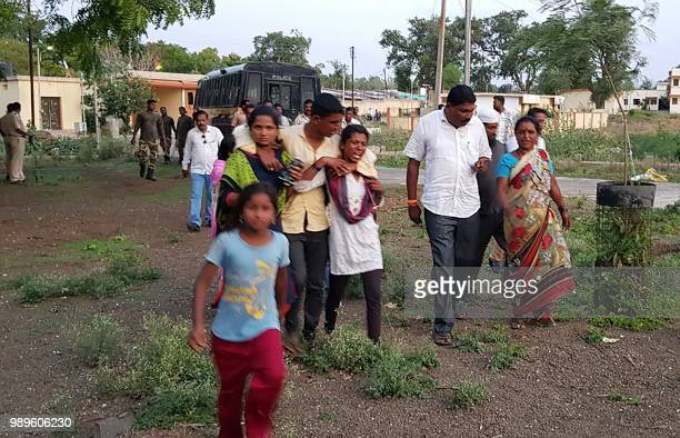 This photo taken on July 1 2018 shows Indian women whose relatives were murdered in a lynching incident being led away from the crime scene area by...