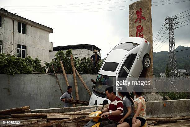 This photo taken on July 10 2016 shows residents looking at a damaged car in the aftermath of a tropical storm in Bandong town in Minqing county east...