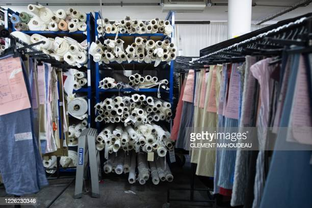 This photo taken on July 10 2020 shows stored rolls of fabric and clothes hanged on a gantry in the Sugar clothes brand factory in Marseille south of...