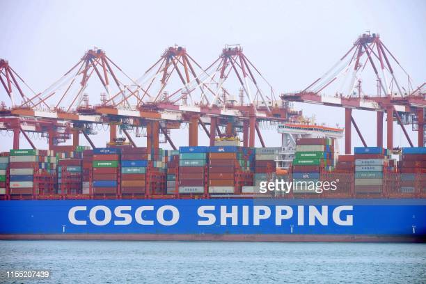 This photo taken on July 11 2019 shows a ship being unloaded at the container port in Qingdao China's eastern Shandong province China's economy grew...