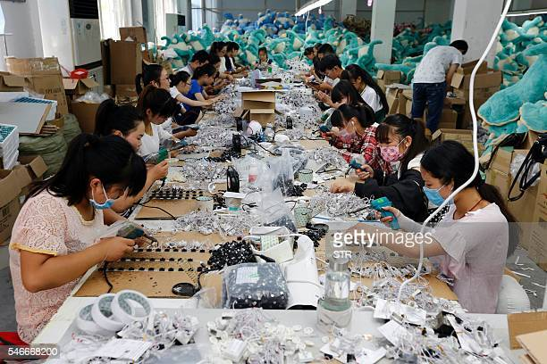 This photo taken on July 12 2016 shows workers in the process of making soft toys at a toy factory in Lianyungang in eastern China's Jiangsu province...