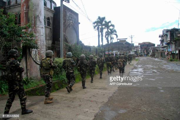 This photo taken on July 12 2017 shows Philippine troops marching towards the frontline where they are battling militants in Marawi on the southern...