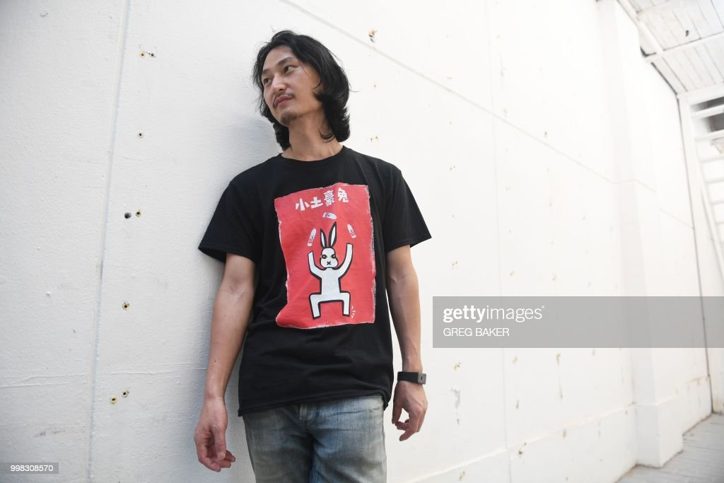 This photo taken on July 12, 2018 shows Chinese performance artist Nut Brother, known for his advocacy work on environmental and social issues, standing in front of an empty wall in a gallery where his exhibition on polluted water was dismantled by authorities from the Industrial and Commercial Bureau, in Beijing. - At first glance, it may seem like just a black truck filled with bottles of water, but a closer look reveals a darker - or rather murkier - side to what's sloshing around inside. Its cargo of more than 500 bottles of Nongfu Spring, a ubiquitous Chinese brand, filled with contaminated drinking water from the village of Xiaohaotu in China's northwest Shaanxi province is being driven around Beijing as a reminder of the costs of China's rapid economic development. (Photo by GREG BAKER / AFP) / TO GO WITH STORY China-environment-art-water-pollution