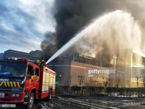 This photo taken on July 12 2018 shows firefighters working to put out a fire after an explosion at a chemical plant in Yibin in China's southwestern...