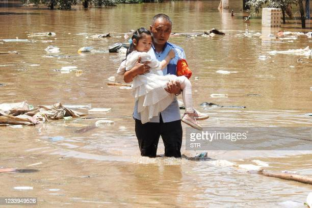 This photo taken on July 12, 2021 shows a village official evacuating a child from a flooded area following heavy rains in Dazhou in China's...