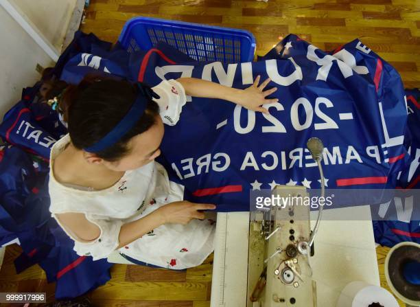 This photo taken on July 13 2018 shows a Chinese employee sewing a banner declaring US President Donald Trump's reelection intentions that reads...