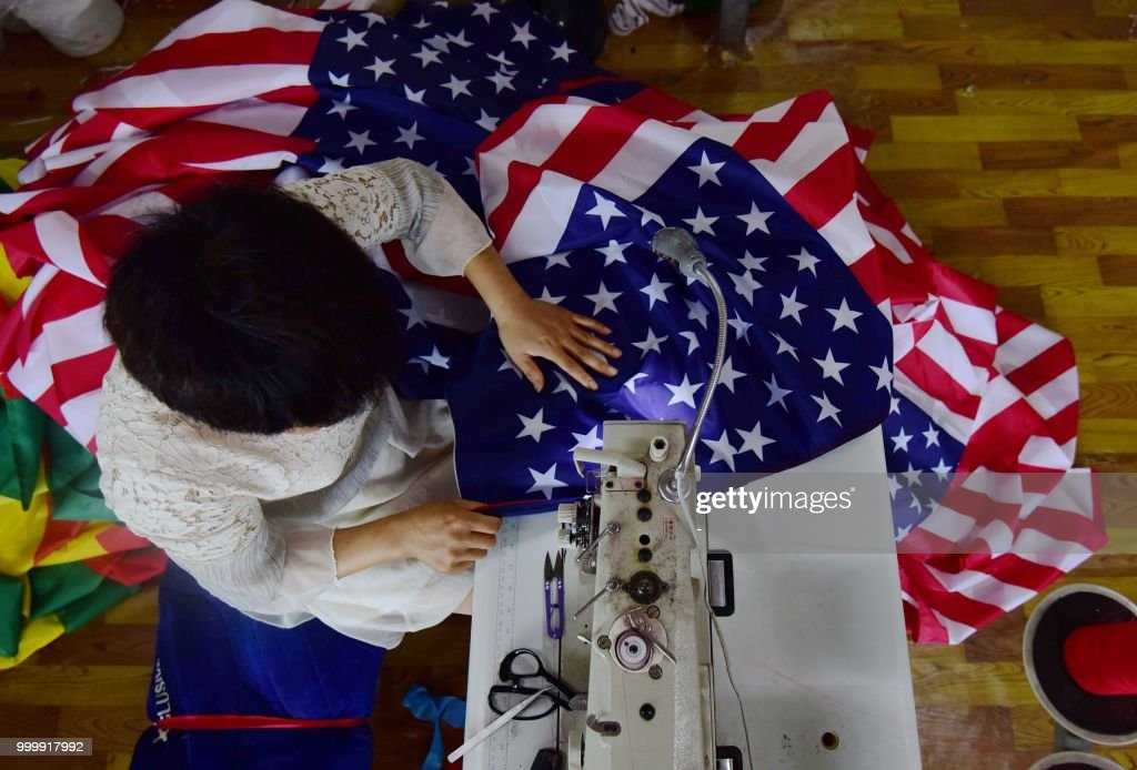 This photo taken on July 13, 2018 shows a Chinese employee sewing a US flag at a factory in Fuyang in China's eastern Anhui province. - As the Sino-US trade war rages, a factory set amid corn and mulberry fields in central China stitches together US and 'Trump 2020' flags -- and business is good. (Photo by - / AFP) / China OUT