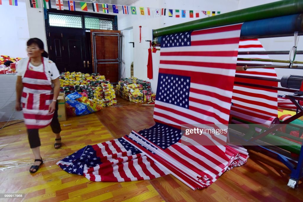 This photo taken on July 13, 2018 shows a Chinese employee walking past newly made US flags at a factory in Fuyang in China's eastern Anhui province. - As the Sino-US trade war rages, a factory set amid corn and mulberry fields in central China stitches together US and 'Trump 2020' flags -- and business is good. (Photo by - / AFP) / China OUT