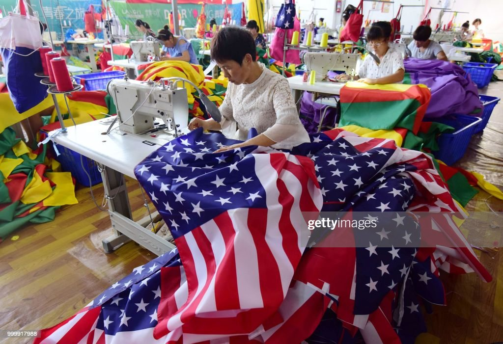 This photo taken on July 13, 2018 shows Chinese employees sewing US flags at a factory in Fuyang in China's eastern Anhui province. - As the Sino-US trade war rages, a factory set amid corn and mulberry fields in central China stitches together US and 'Trump 2020' flags -- and business is good. (Photo by - / AFP) / China OUT