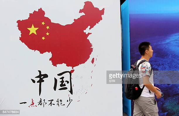 This photo taken on July 14 2016 shows a man walking past a poster of a map with a dotted line showing China's claimed territory in the South China...
