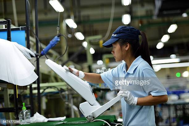 This photo taken on July 14 2016 shows a worker checking a toilet seat at a factory in Hangzhou east China's Zhejiang province China's growth slipped...