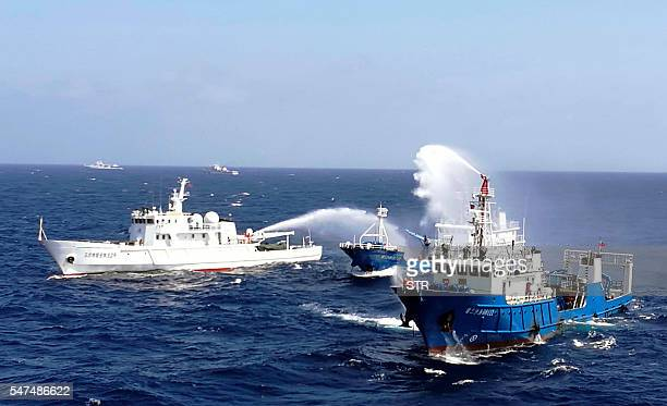 This photo taken on July 14 2016 shows Chinese ships putting out a fire on a mock cargo vessel during an emergency drill in the South China Sea near...